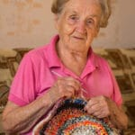 An old woman sits knitting a rug.